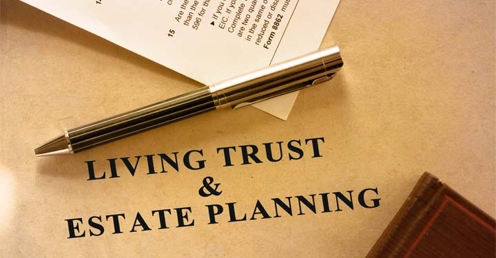 "Paper labeled ""Living Trust and Estate Planning"" and a pen on top"