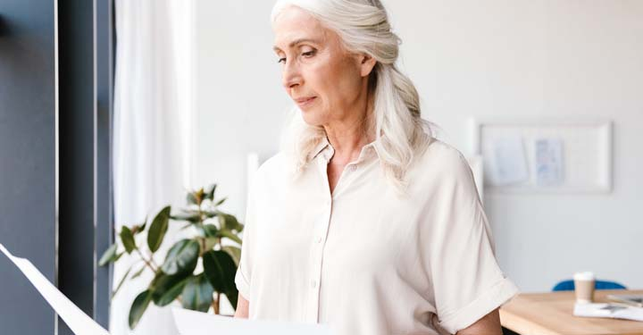 Older woman looking at paper while standing in front of window in room containing plant and table with coffee cup placed on it