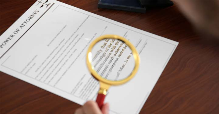 """""""Power of Attorney"""" document under magnifying glass"""