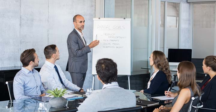 """Businessman standing in front of team in conference room gesturing to paper pad that says """"annual goals"""""""