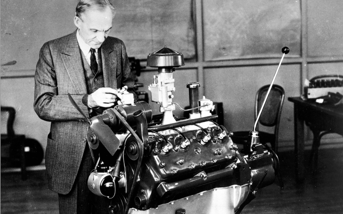 Henry Ford, looking at an engine