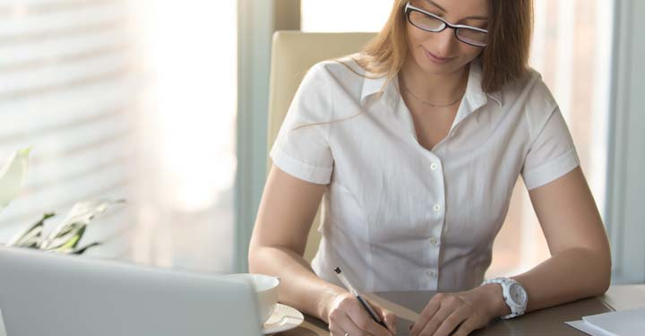 Woman writing with ballpoint pen next to coffee cup in front of laptop