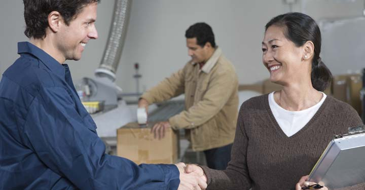 A supplier and a distributor shaking hands in a factory