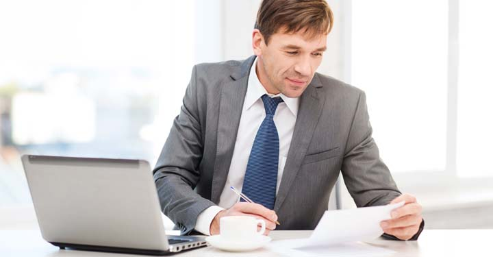 Man holding a piece of paper and pen working at a desk with a laptop and cup of coffee