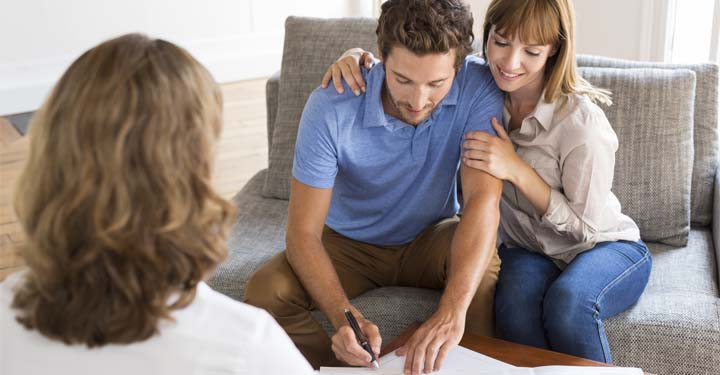 Couple on gray couch signing document in front of woman