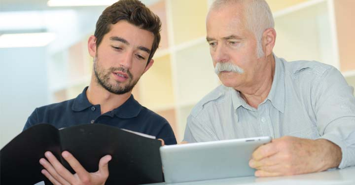 Young man with binder and elderly man with tablet comparing information