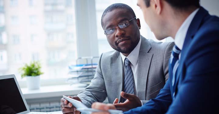 Two men in suits talking in office