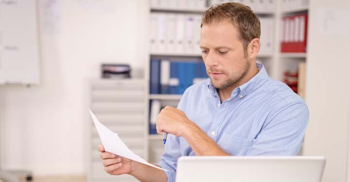Man holding a piece of paper and reading from it