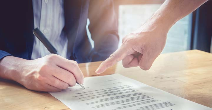 Person signing a document with another person's hand pointing at the paper