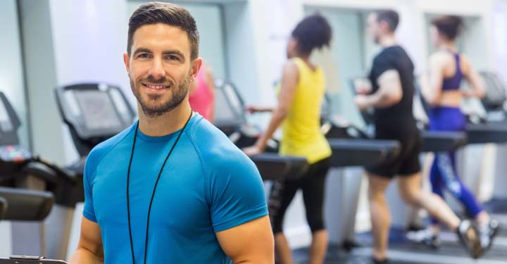 Man smiling in gym with people running on treadmills in the background