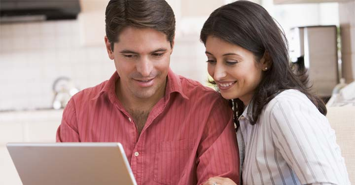 Couple in kitchen gazing at iPad