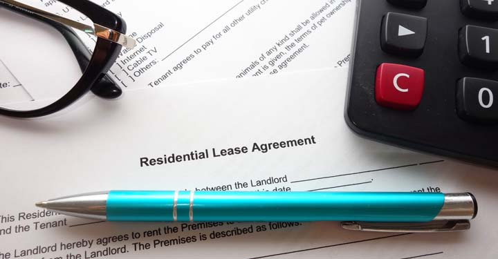 A pair of glasses, a blue ballpoint pen, and a calculator resting on a residential lease agreement
