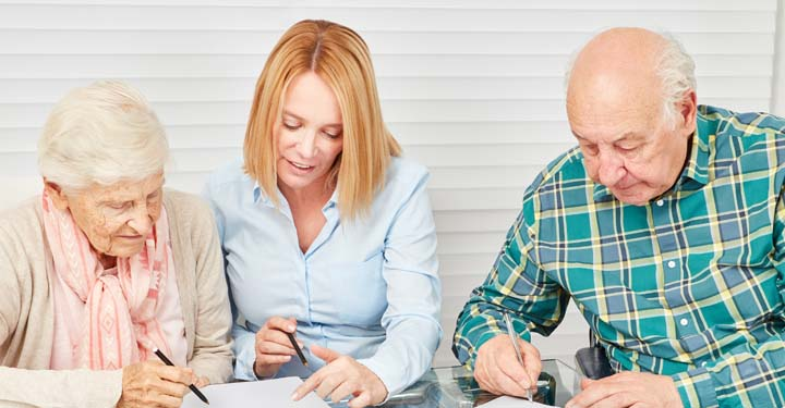 Woman helping an elderly couple sign documents