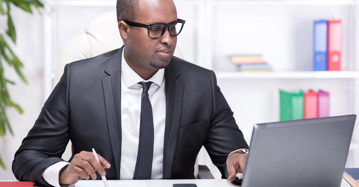 Man in suit holding pen and typing on laptop while at desk