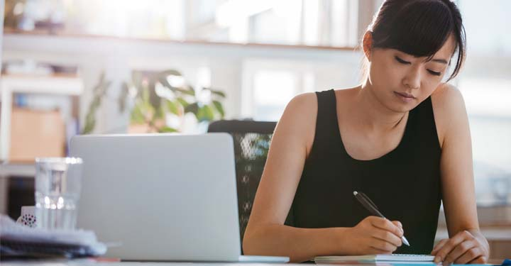 Woman in office in black tank top writing in notebook in front of laptop