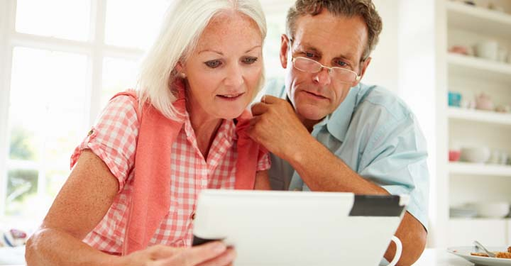 Older couple in kitchen looking at iPad