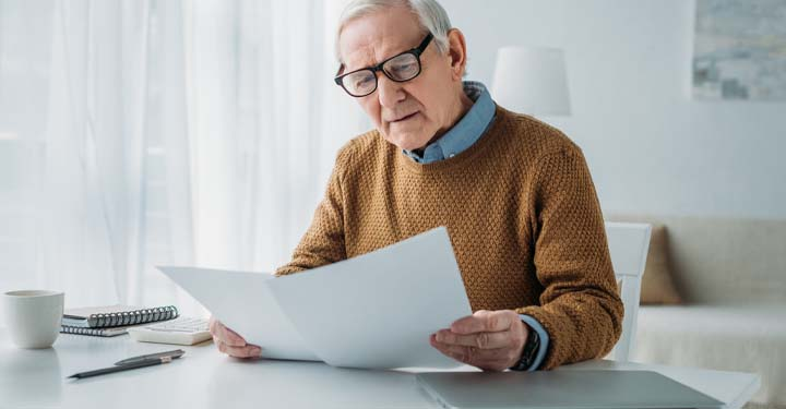 Old man in black glasses, blue button down, black watch, and yellow sweater looking at two sheets of paper on white desk