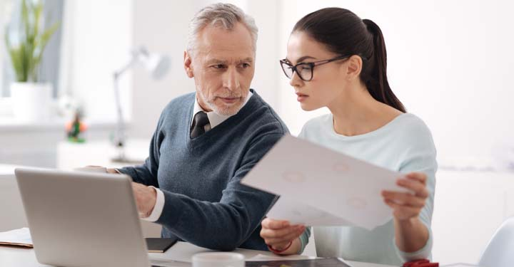 Middle aged man in office points to computer while looking at young woman looking at computer and holding papers