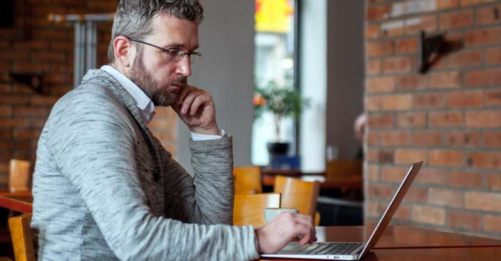 Man in café looking intently at laptop