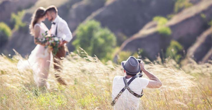 Wedding photographer taking pictures of a bride and groom in a field