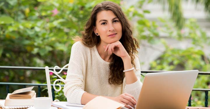 Woman resting chin on hand and typing on laptop sitting outside