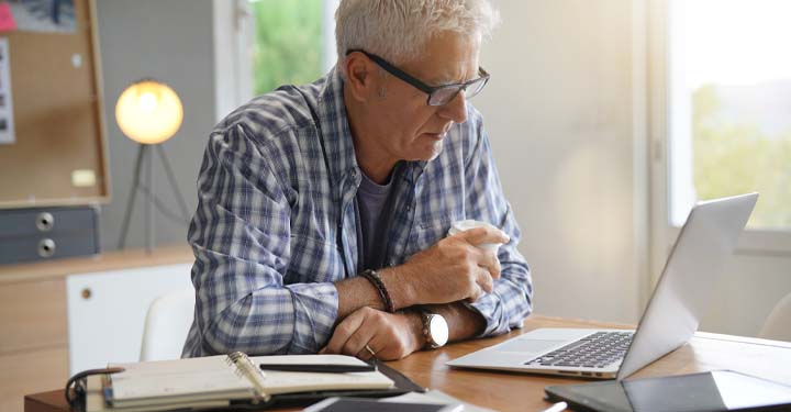 Man sitting at a table holding a cup of coffee looking at his laptop next to an open notebook