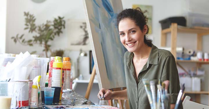 Female artist sitting in studio next to paints and paintbrushes in front of painting on canvas