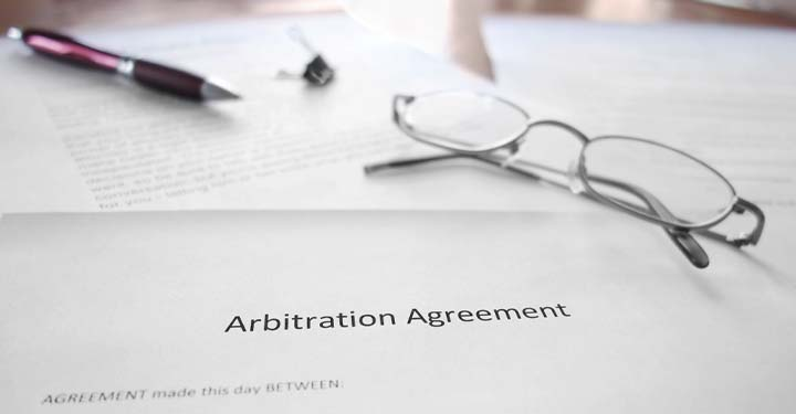 """Glasses, pen, and binder clip on papers focusing on text """"arbitration agreement"""""""