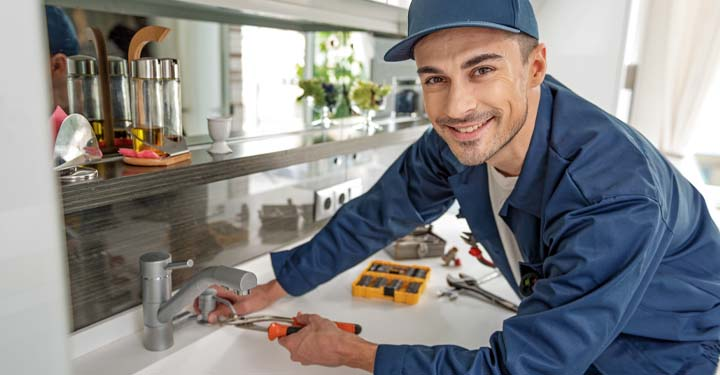Man in kitchen using tools to fix sink