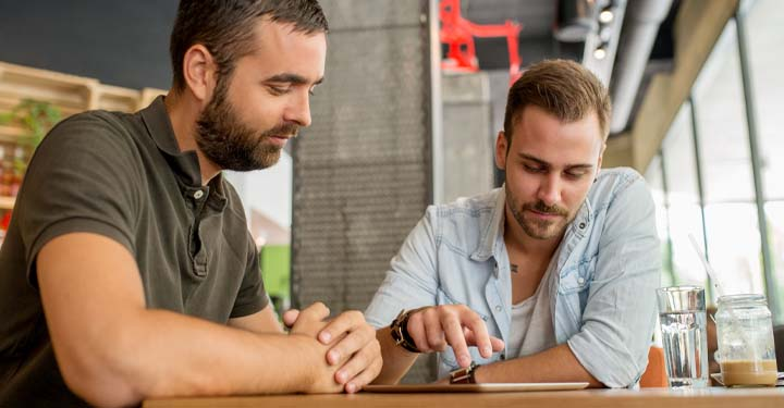 Two bearded men in cafe look down at iPad