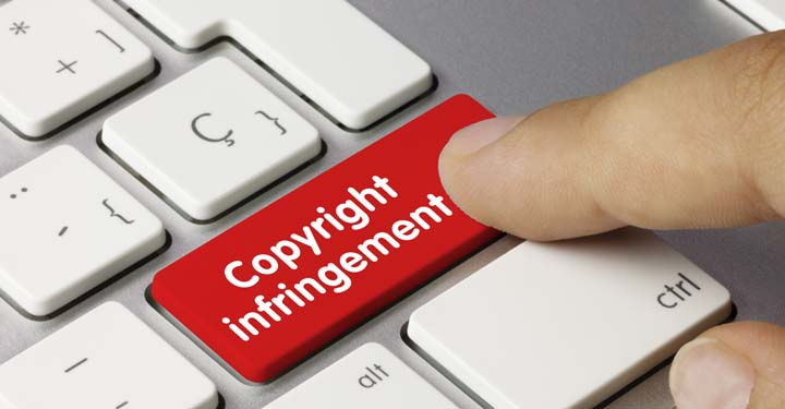 "Finger pressing red button on computer keyboard with white text ""copyright infringement"""