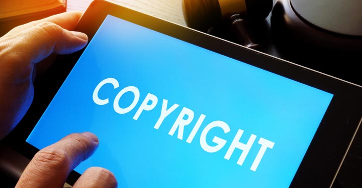 """Hands holding a tablet with the word """"copyright"""" displayed on the screen"""
