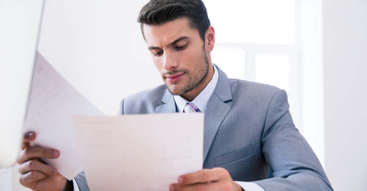 Businessman appearing confused while sifting through papers