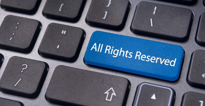"Computer keyboard with one blue key labeled ""All Rights Reserved"""