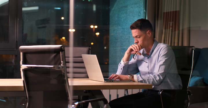 Concerned businessman sitting alone in front of laptop in sleek office at night in front of glass window showing city lights