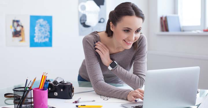 Woman with short brown hair in art studio leans across desk with art supplies and camera on it to type on laptop