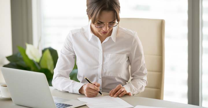 Woman in office holds pen above form at desk with laptop