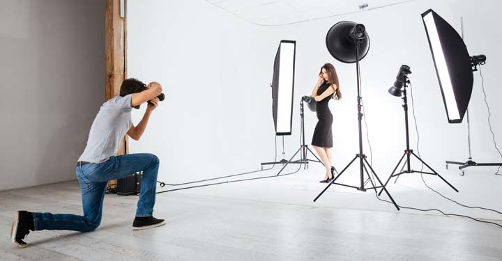 Photographer on his knee taking photos of a woman surrounded by lighting and a white backdrop