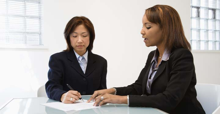 Two businesswomen sitting at a table reviewing a document