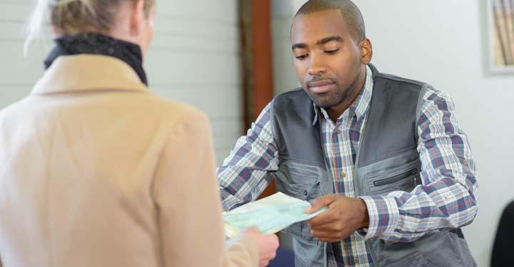 Woman handing a man paperwork