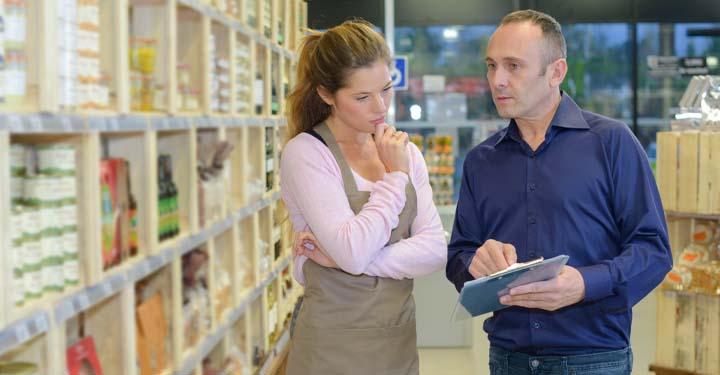Man with clipboard talking to woman with apron in supermarket