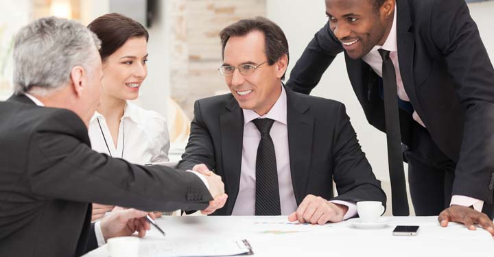 Four businesspeople make an agreement above documents on white desk as two people shake hands