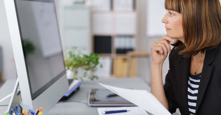 Woman looking intently at desktop computer holding a piece of paper