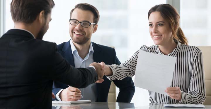 A smiling couple sitting across from a businessman.  The woman holds paperwork and shakes the businessman's hand.