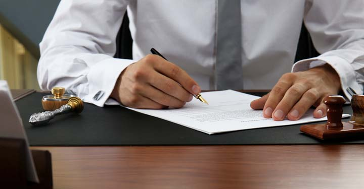 Businessman's hands signing a document