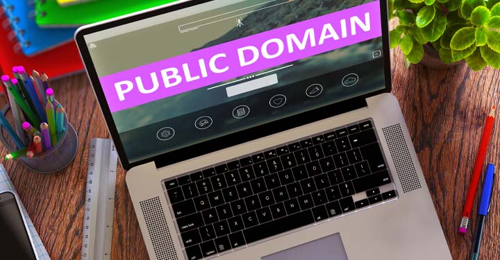 """Open computer sitting on a desk with the words """"public domain"""" on the screen"""