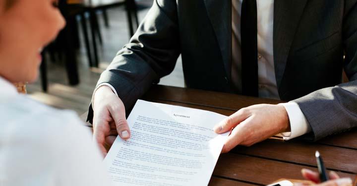 Man handing a woman an intellectual property assignment agreement