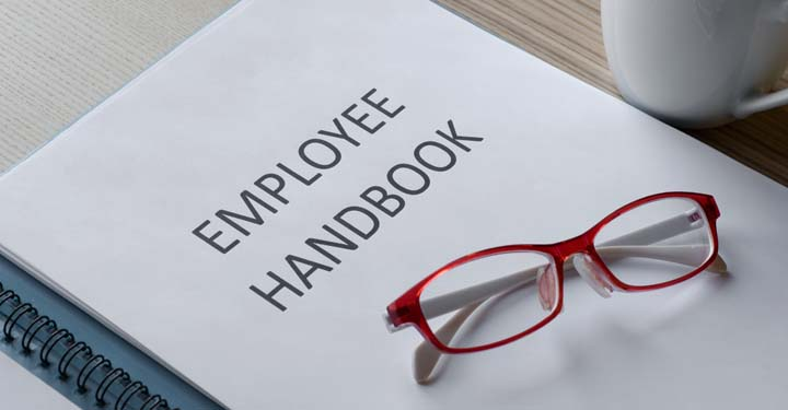"Stack of papers labeled ""Employee Handbook"" with a pair of glasses sitting on top"