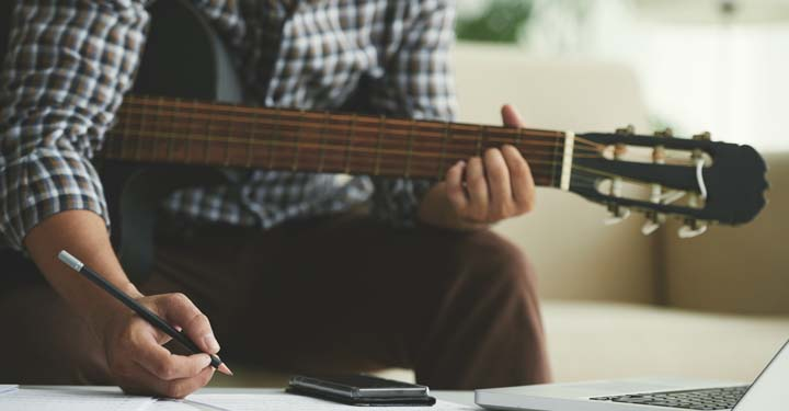 Man holding guitar writing with a pencil