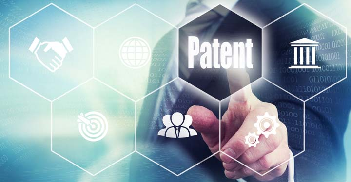 "Businessman selecting hexagon on glass screen containing word ""patent"" surrounded by other hexagons containing business-related symbols"